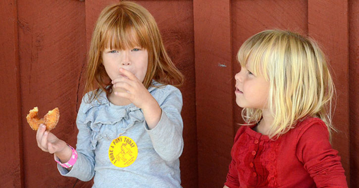 two little girls, one is eating a doughnut