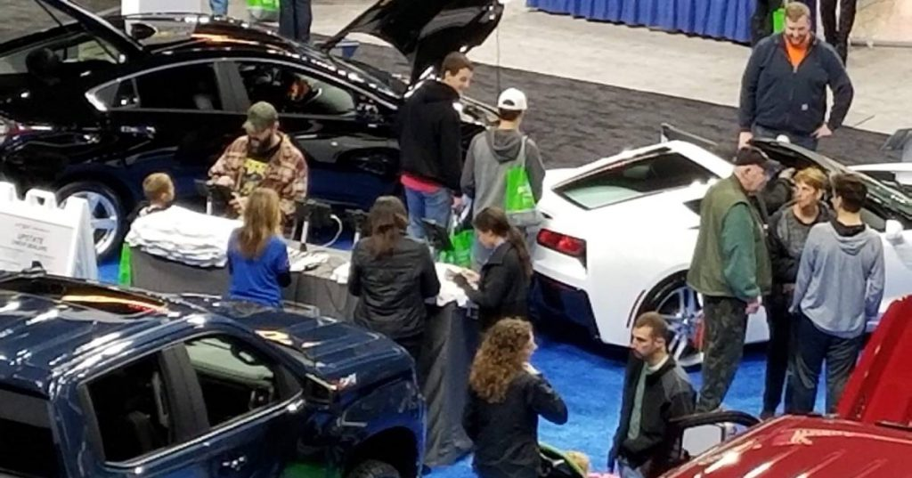 people checking out cars at indoor show