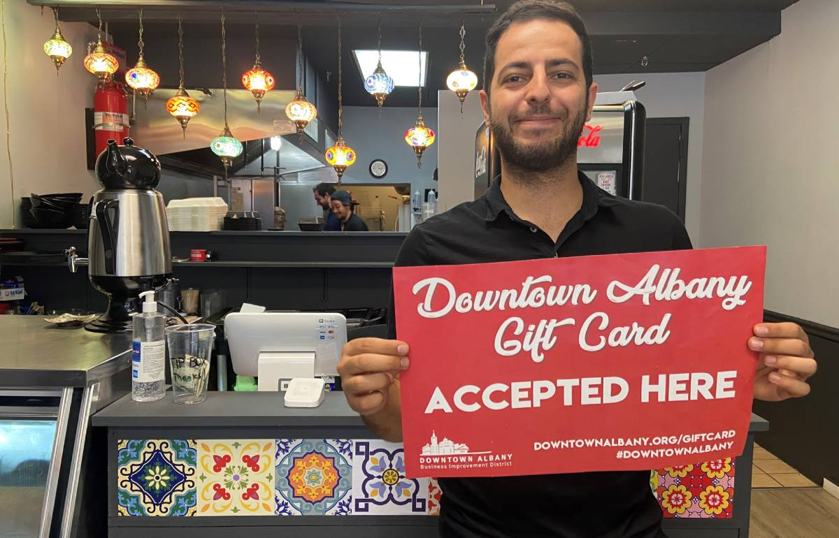 man holding up a red downtown albany gift card sign inside a restaurant