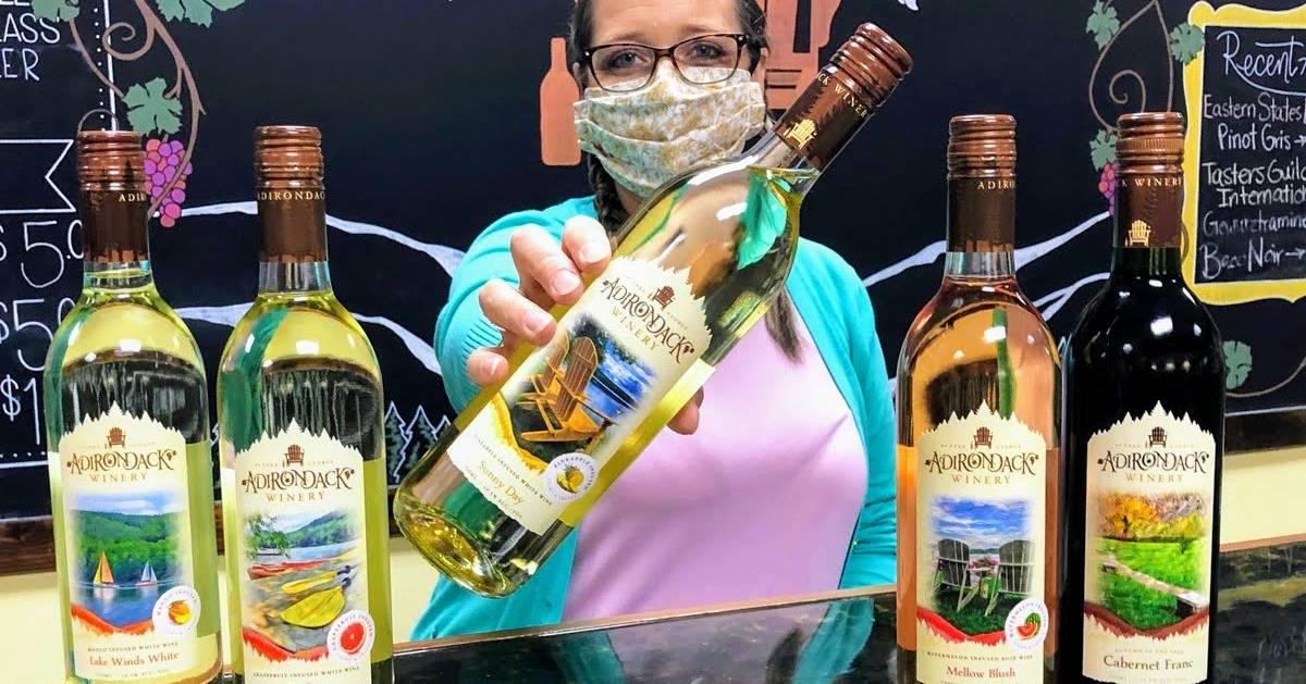 masked woman holding out Adirondack Winery wine bottle