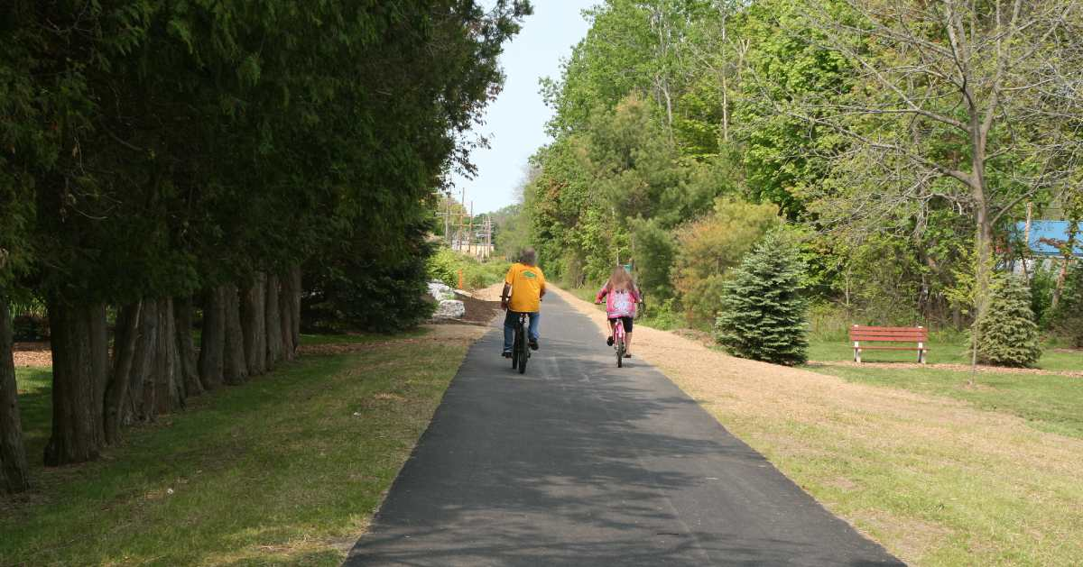 two people riding bikes down paved trail
