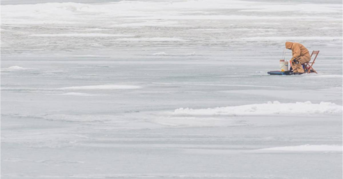 person on frozen lake ice fishing