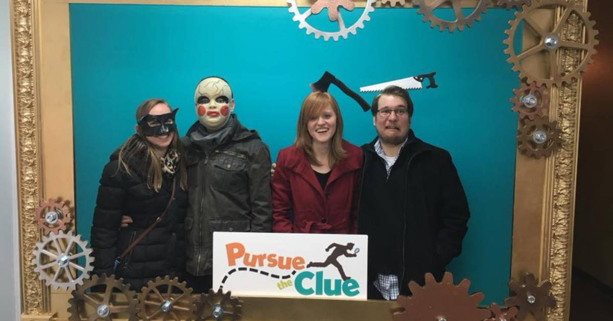 four people with props and a pursue the clue sign