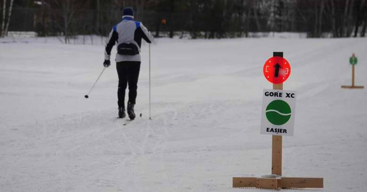 man cross country skiing with sign near a trail