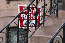 For Rent sign on the steps of a brownstone