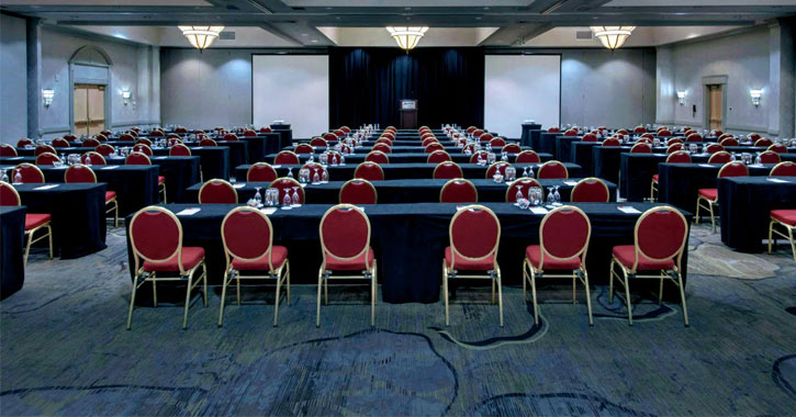 a large conference room with rows of tables and chairs set up