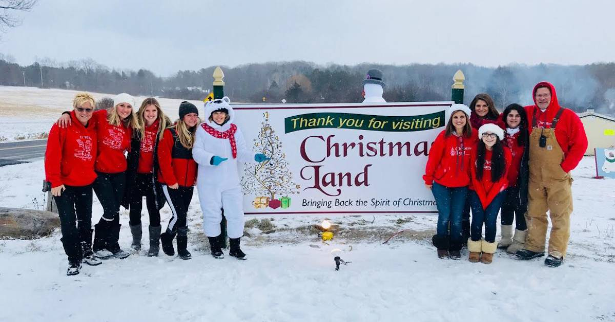 people near christmas land sign