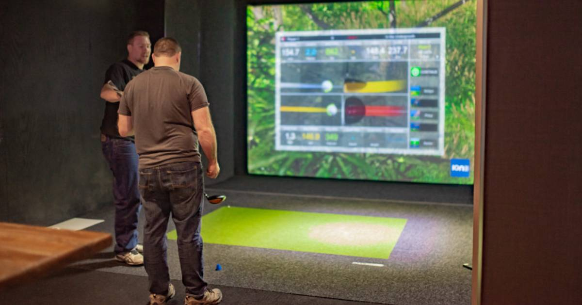 two men at a golf simulator screen