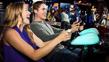 a couple playing an arcade game and laughing