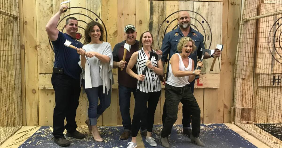 group of people holding up axes in front of axe throwing targets