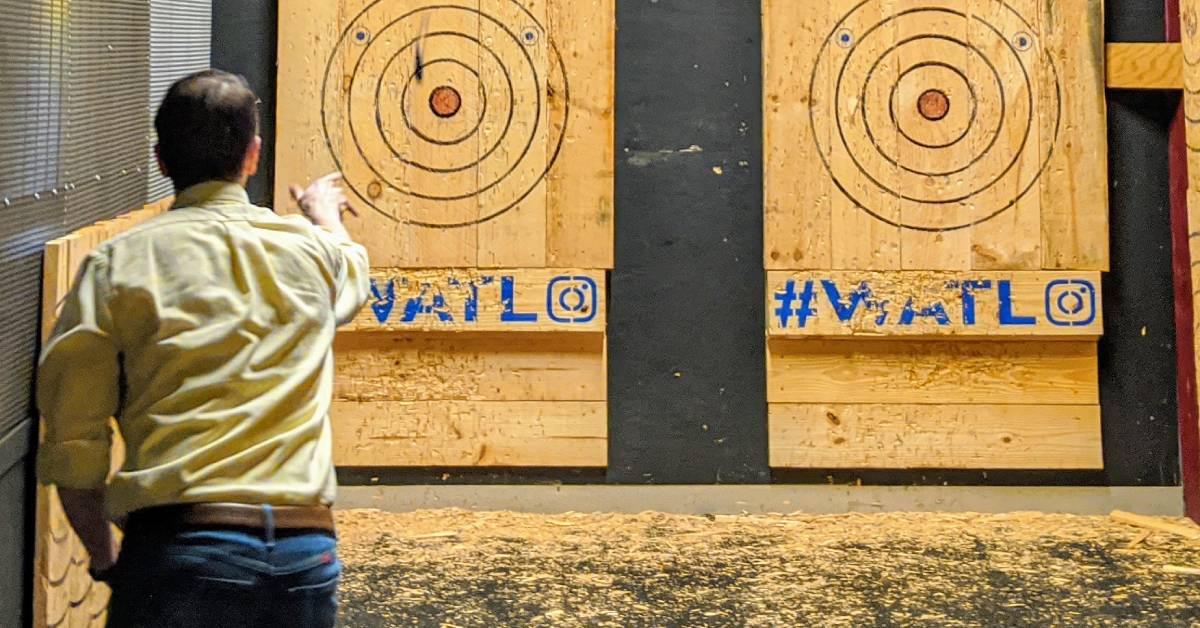 man throwing axe at a wooden target with a bullseye on a wall