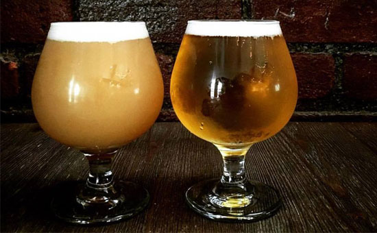 two beer goblets against a brick wall