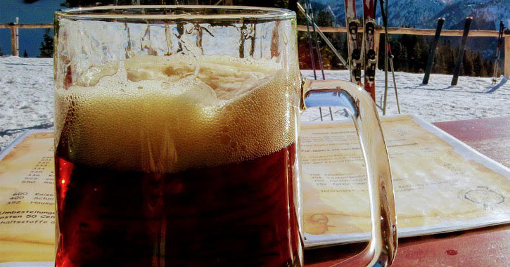 a mug of beer with a backdrop of snow and mountains