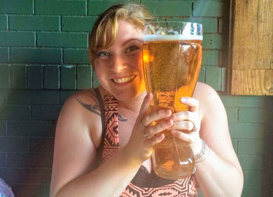 woman smiling and holding up a giant boot of beer