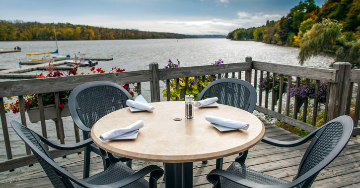 a table and chairs set up on a deck by the water on a beautiful day