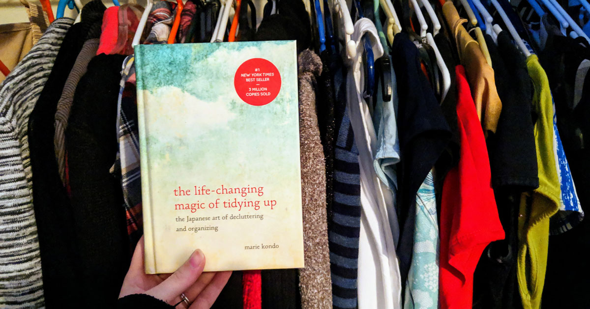 Marie Kondo book held in front of clothes in closet