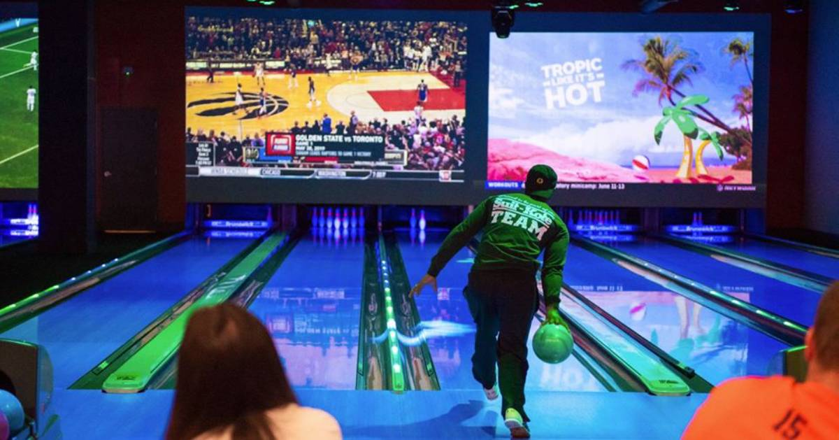 man bowling at bowling alley with tv screens in front
