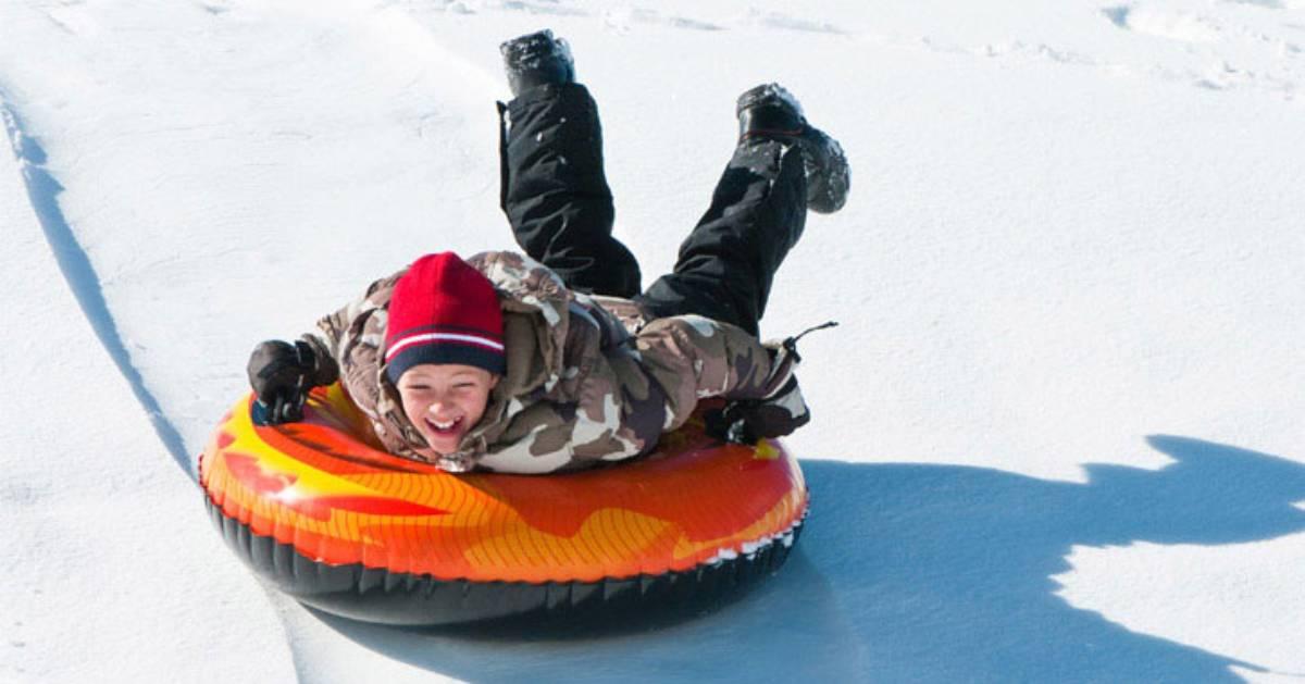 a boy snow tubing down a hill