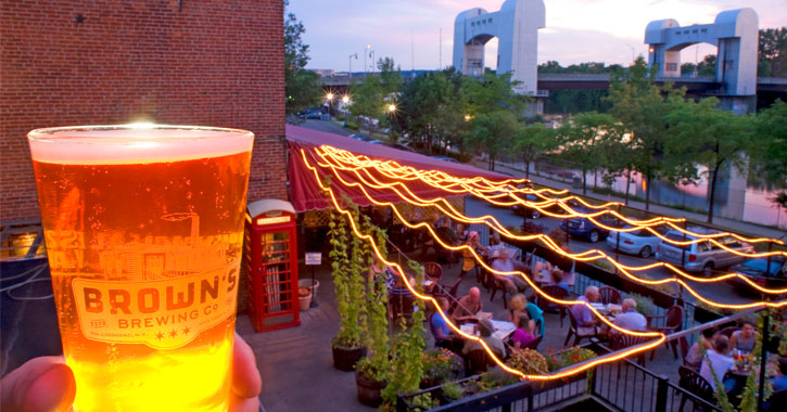 a beer of Brown's Brewing held up againt a backdrop of people on the patio