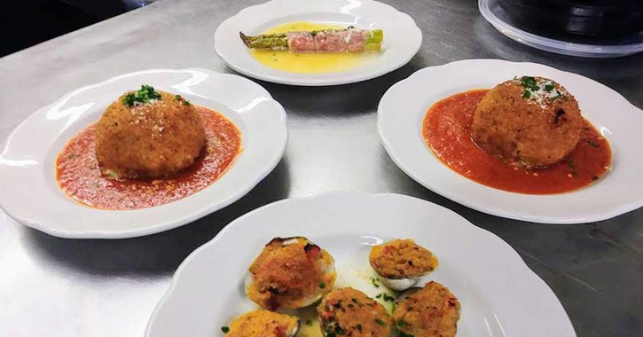 four plates, two with a giant meatball, one with asparagus, one with what looks like breaded clams