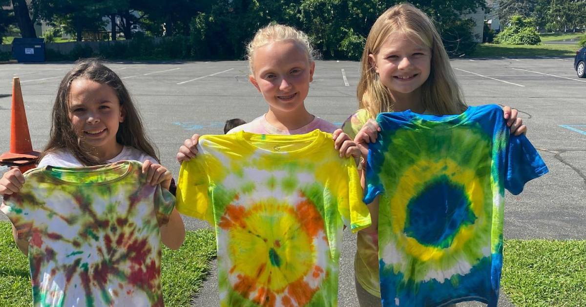 three young girls holding up tye dye shirts