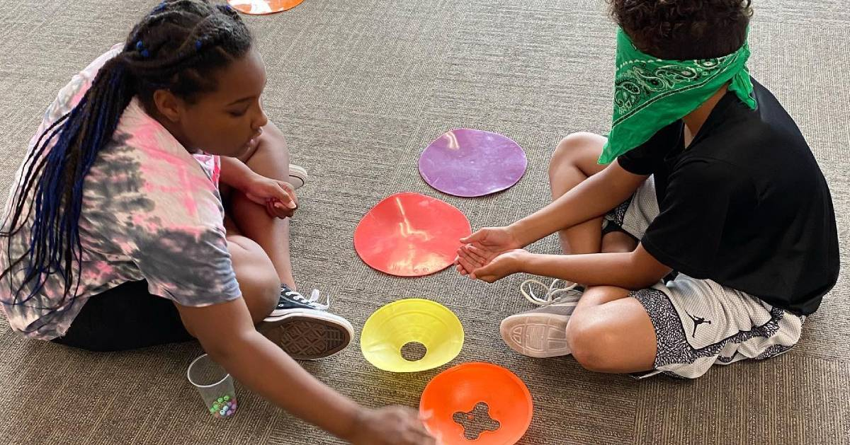 two kids on the floor playing some kind of game with colored plates