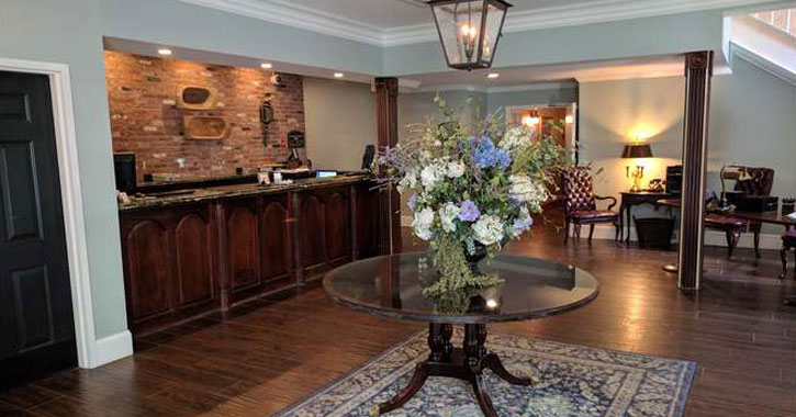 what looks like the lobby area in a hotel with fresh flowers on a round table in the center