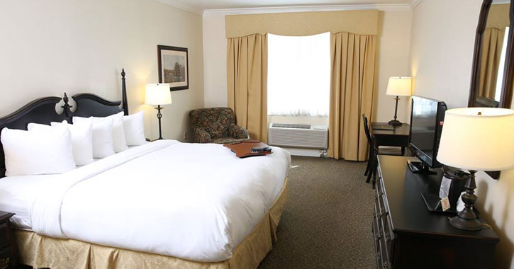 a large bed in a hotel room with typical hotel furniture and a large window