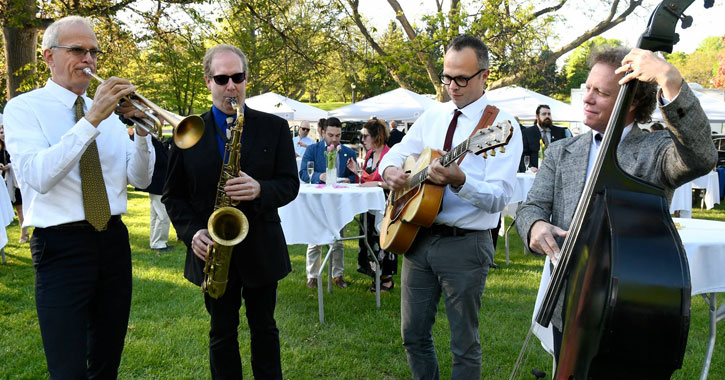 a quartet playing in the park, vendor tents and tables set up
