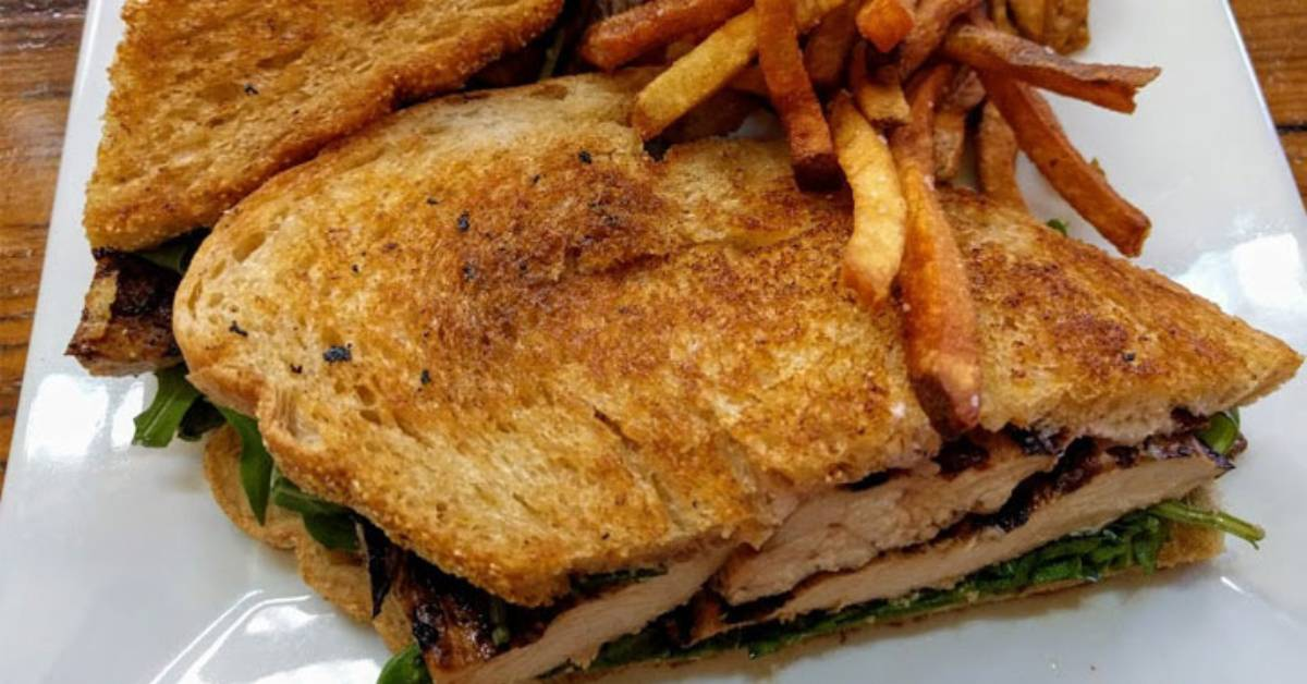 a chicken sandwich with fries on a white plate