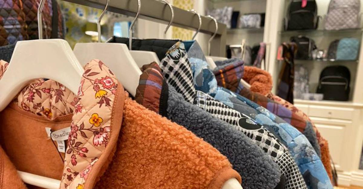 fuzzy vests and coats on a clothing rack in a store