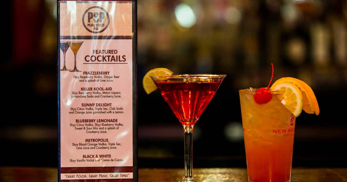 cocktail menu next to two cocktails on a bar