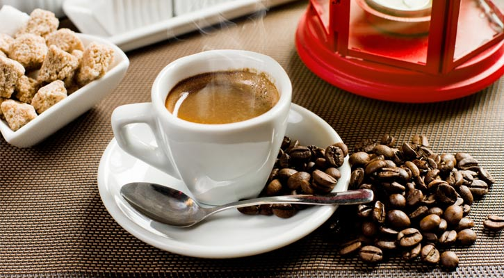 a cup of coffee with coffee beans spillin goff the saucer, what looks like scones to the left, and a small white candle in a red container on the right
