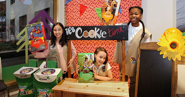 three girl scouts at a cookie booth