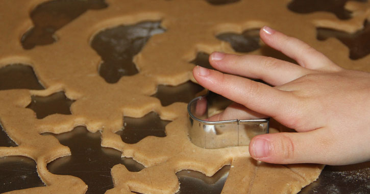 a little kid's hand making shapes in dough from a cookie cutter