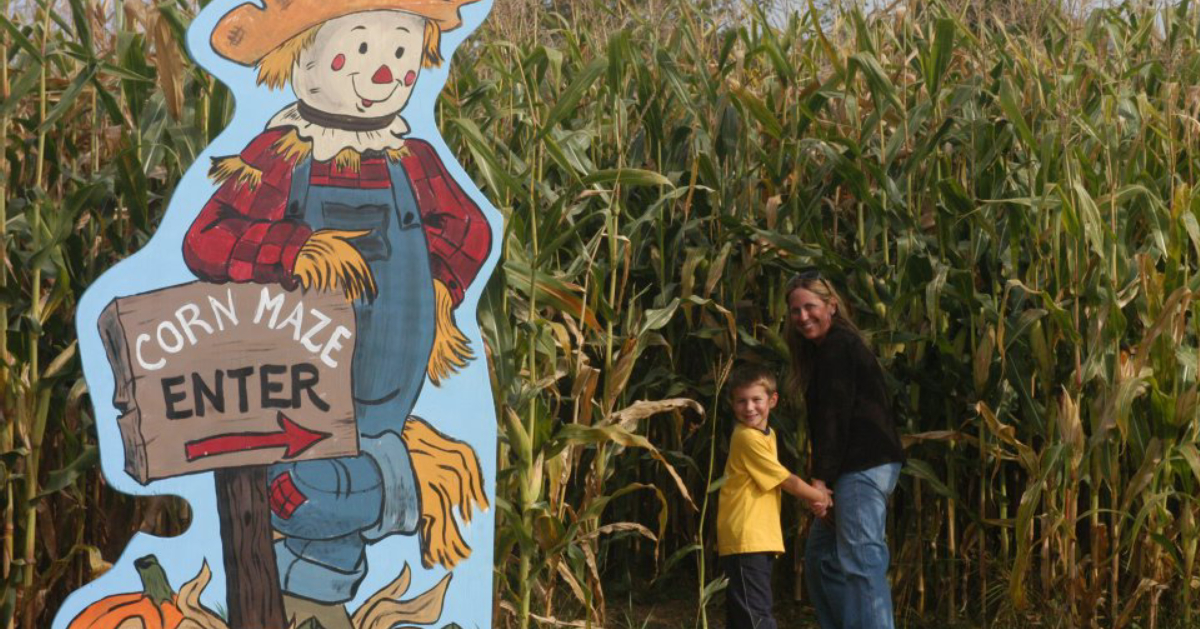 corn maze sign and two people
