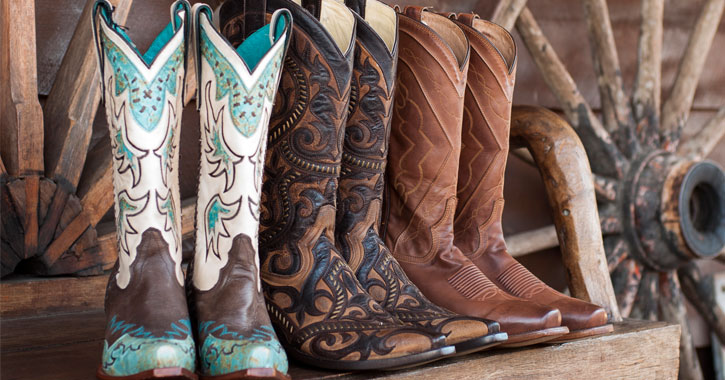 three pairs of western-style boots lined up on a wooden bench