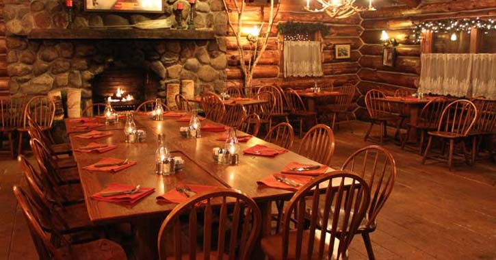 wooden tables and chairs set up in an Adirondack-style restaurant with a fire in a stone fireplace