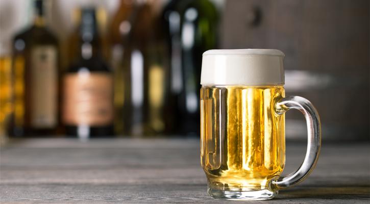 a large mug of light beer, bottles in the background