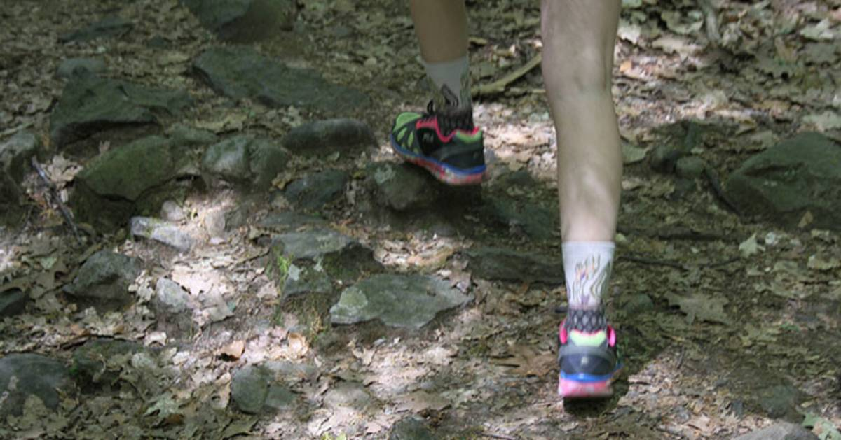 legs of a hiker on a trail