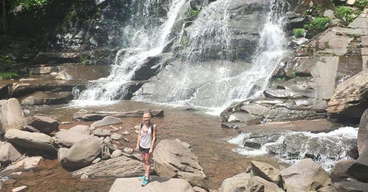 woman standing near bottom of waterfall