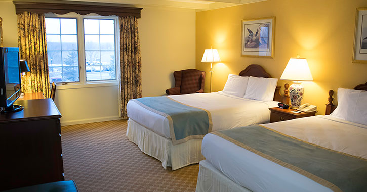 two beds in a brightly lit hotel room