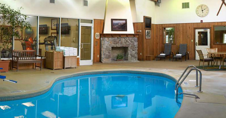 an indoor pool inside a hotel with a stone fireplace and wood panneled walls