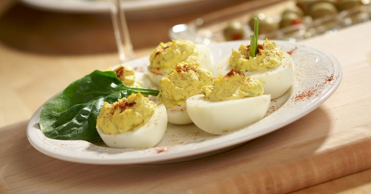 deviled eggs on a plate with what looks like a spinach leaf garnish