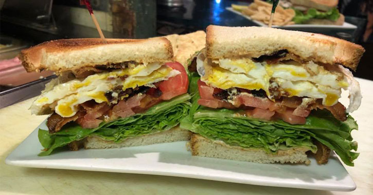 two sandwiches stuffed with bacon, lettuce, eggs, etc.