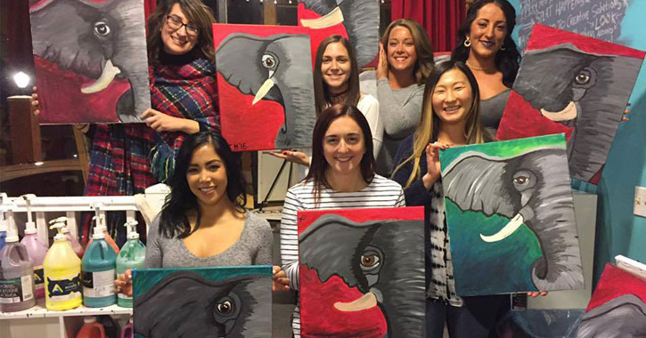 group of women at paint and sip holding up paintings of elephants