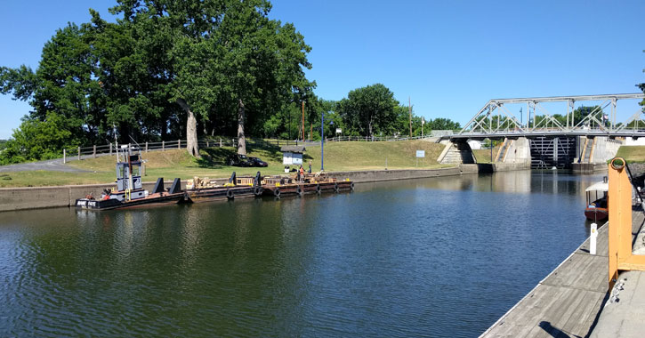 view of Erie Canal in Waterford on a clear day with a boat and a bridge
