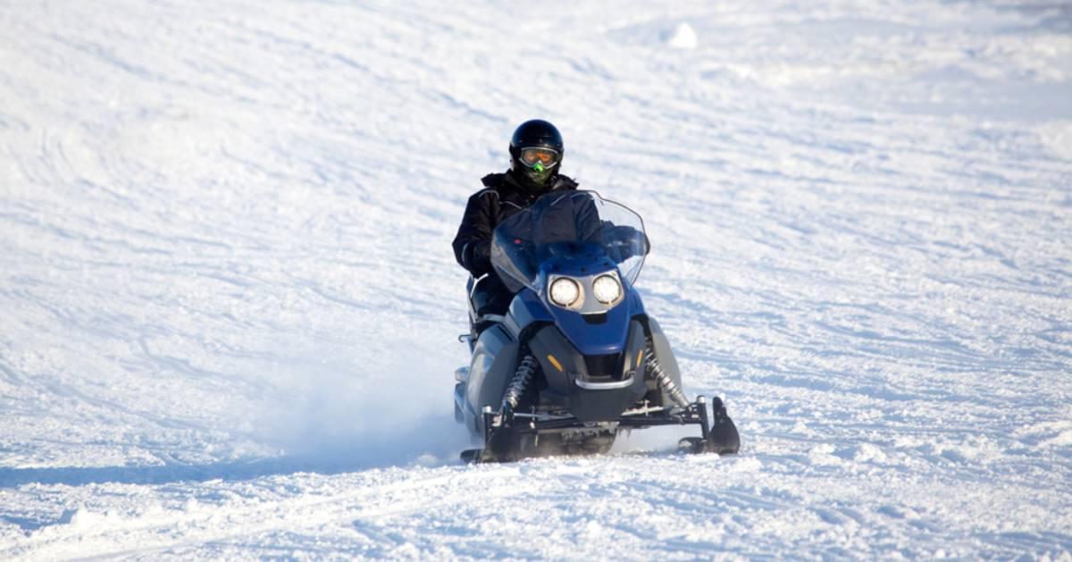 snowmobiler riding across snowy ground