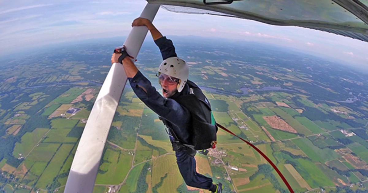 skydiver holding onto a plane