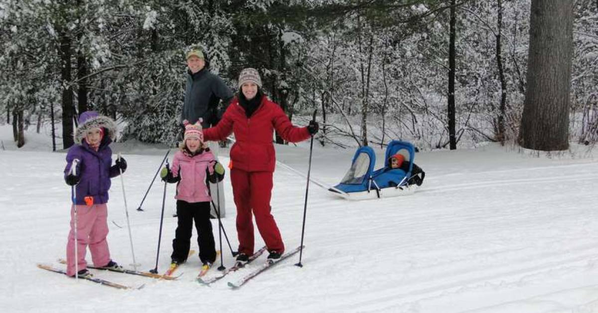 a family of skiers on a snowy trail